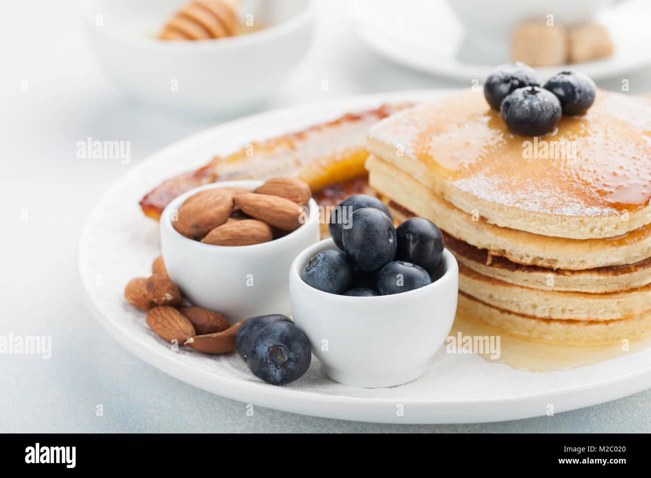 Una pila de deliciosas tortitas con miel, café y arándanos sobre un fondo azul claro. Gran desayuno para el día Foto de stock