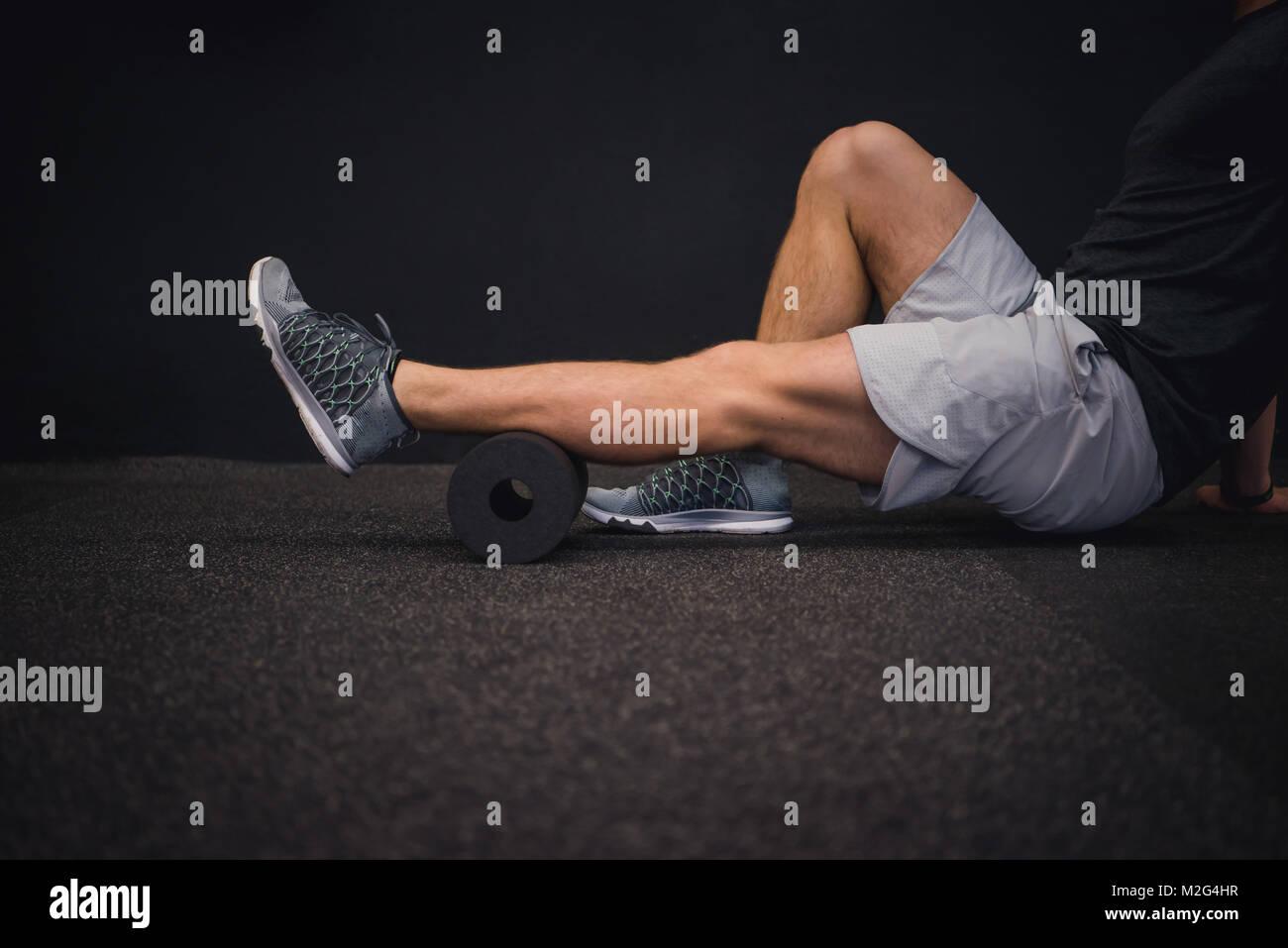 Athletic hombre utilizando un rodillo de espuma para aliviar los músculos doloridos después de un entrenamiento. Imagen De Stock