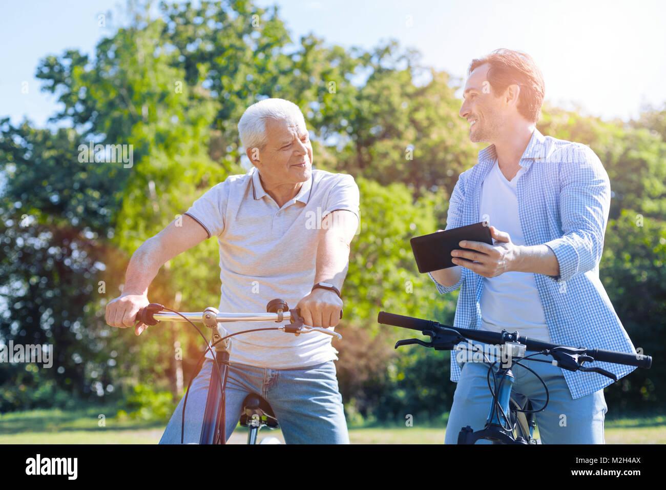 Padre e hijo con touchpad montando sus bicicletas. Imagen De Stock