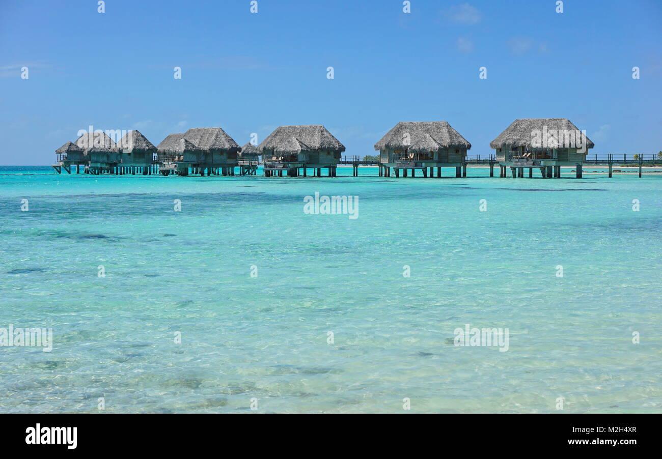 Overwater bungalows tropicales en una laguna de aguas color turquesa, Tikehau atoll, Tuamotus, Polinesia francesa, Imagen De Stock