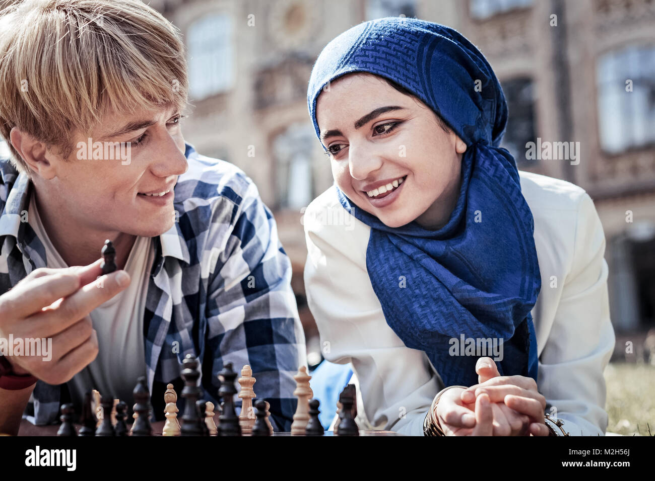 Encantado positivo una mujer mirando la pieza de ajedrez Foto de stock