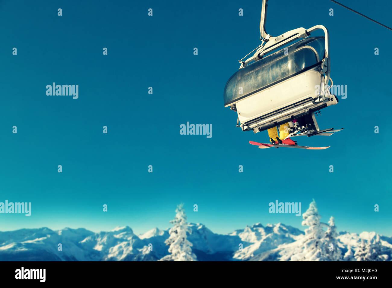 La gente en telesilla en la estación de esquí por encima de árboles nevados y montañas Foto de stock