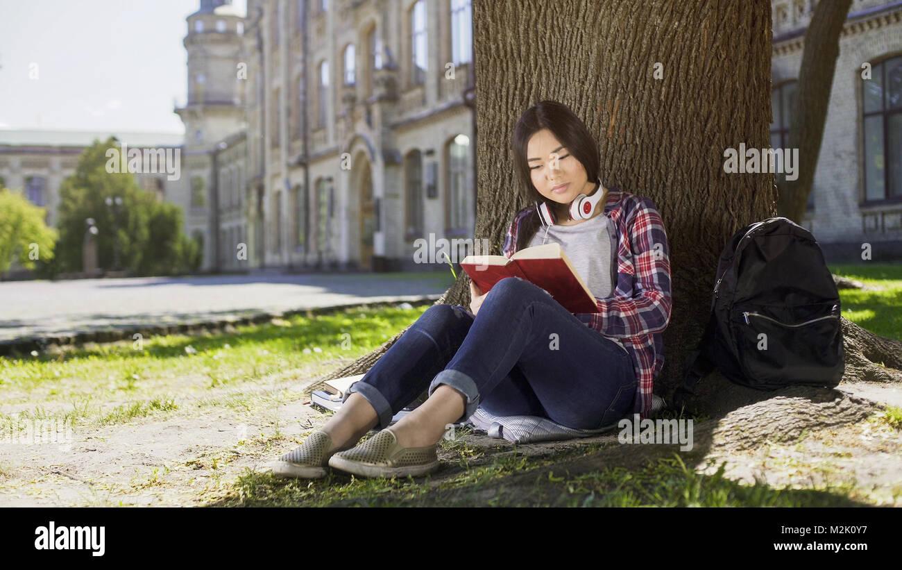 Hembra mixtos sentado bajo el árbol, leyendo el libro favorito, la apasionante trama, absorto Imagen De Stock