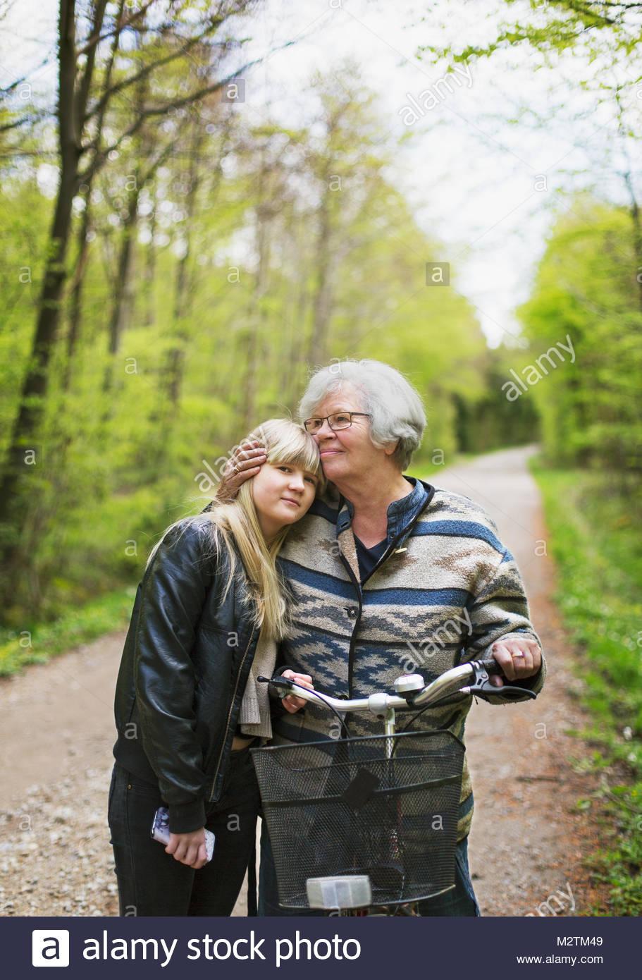 Abuela y nieta abrazando el camino forestal Imagen De Stock