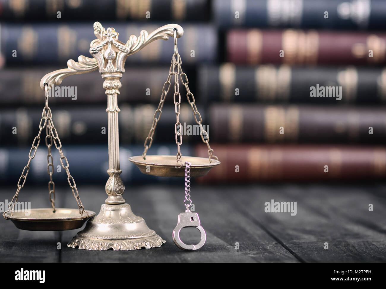 La ley y la justicia, el concepto de legalidad, escalas de justicia y esposas sobre un fondo de madera negra. Foto de stock