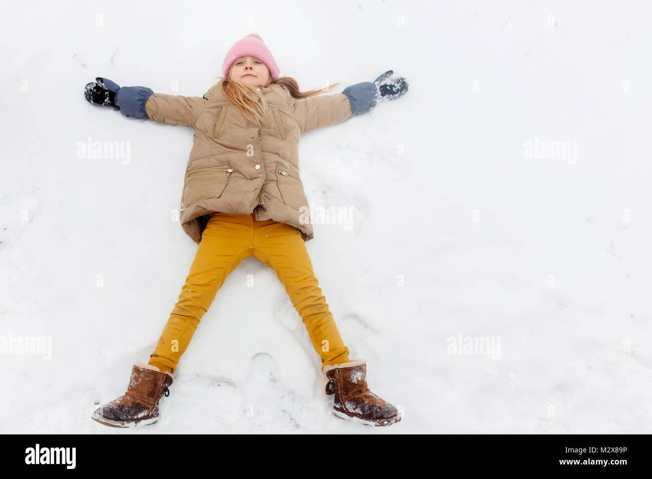 Foto de chica acostada en la nieve en park Imagen De Stock