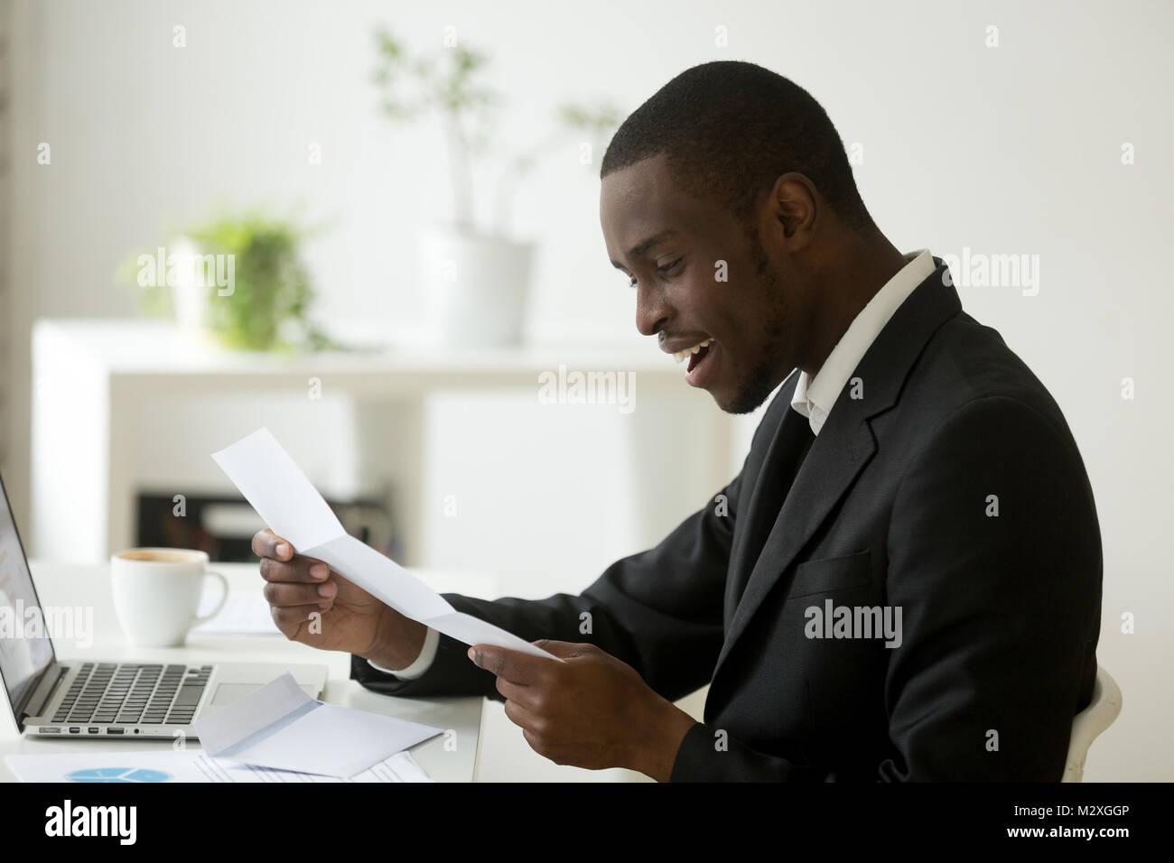 Empresario de traje negro feliz leyendo el correo carta entusiasmados por buenas noticias sentado en la oficina, Imagen De Stock