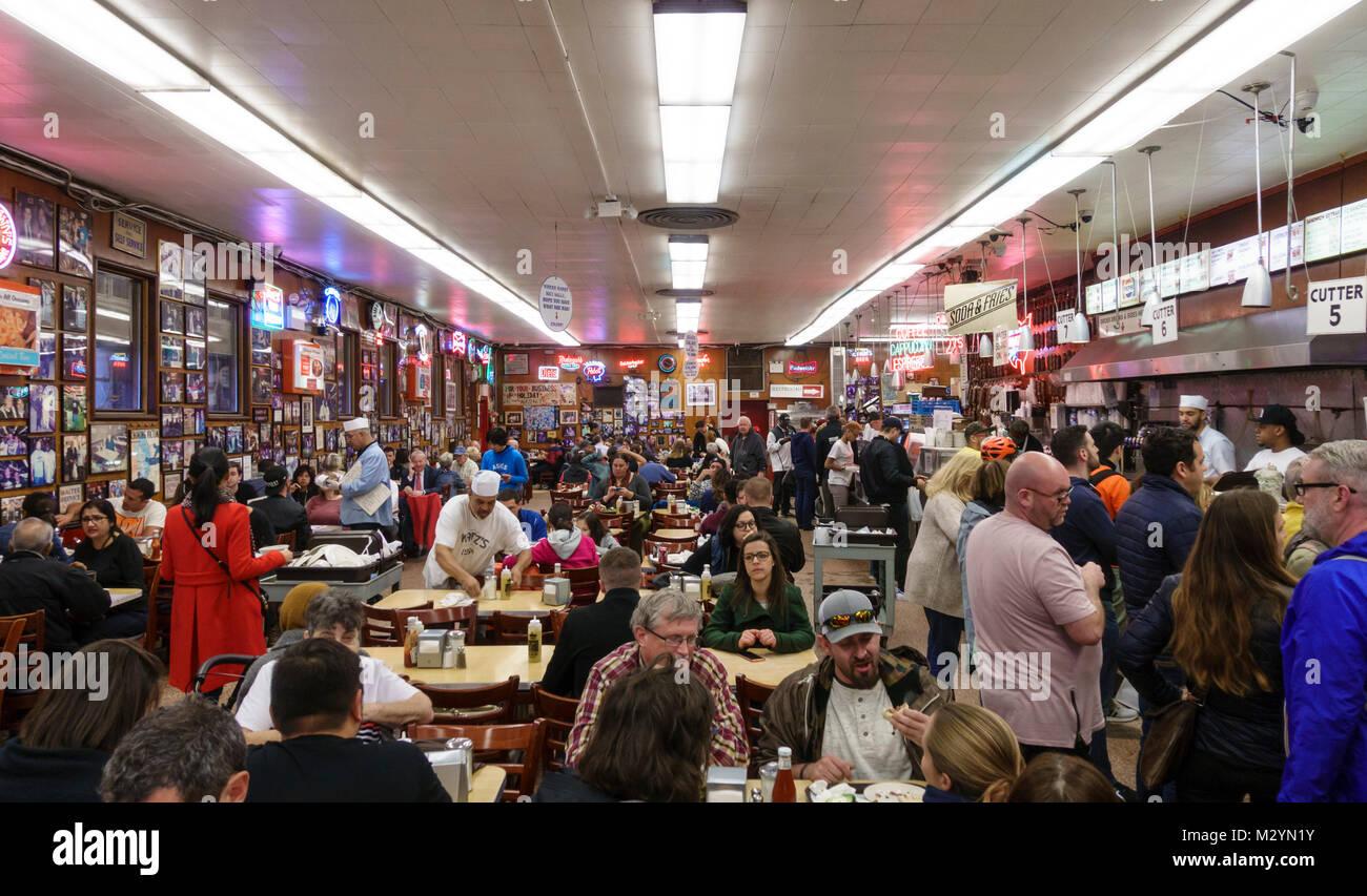 Los clientes y servidores camareros en la zona ruidosa y concurrida comedor a Katz's delicatessen, un famoso Imagen De Stock