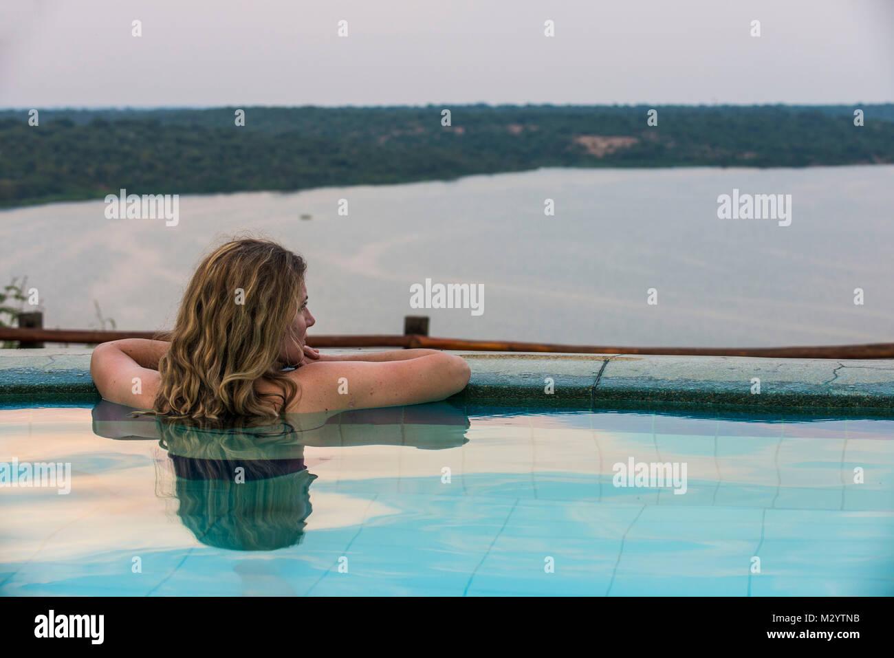 Mujer en una relajante piscina encima del canal Kazinga en el Parque Nacional Queen Elizabeth, Uganda Imagen De Stock