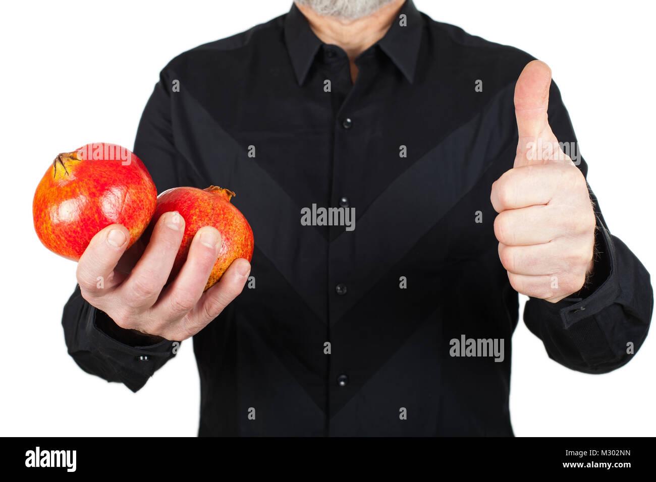 Cerrar imagen de hombre de negro sujetando la granada madura, alto de frutas antioxidantes, mostrando Thumbs up Imagen De Stock