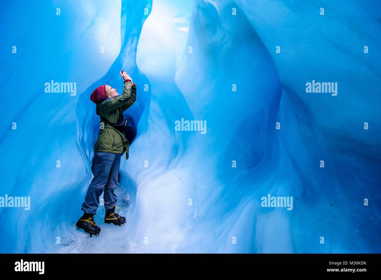 Mujer fotografiando en una cueva de hielo en el glaciar Fox, Isla del Sur, Nueva Zelanda Foto de stock