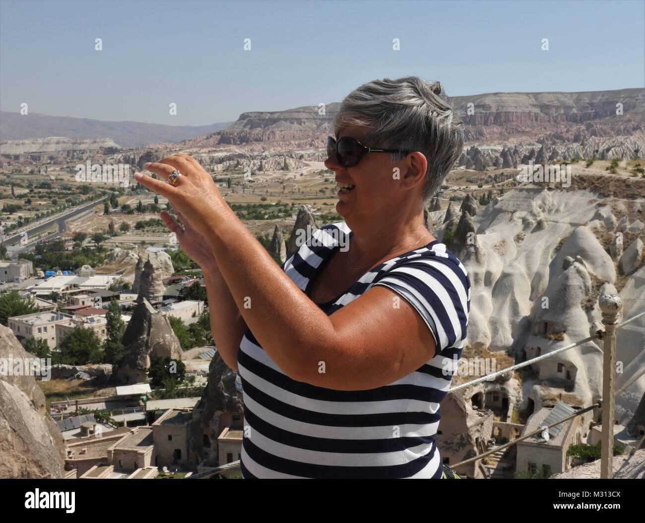 Una señora inglesa turista tomando fotos del impresionante goreme, Capadocia en Turquía Foto de stock