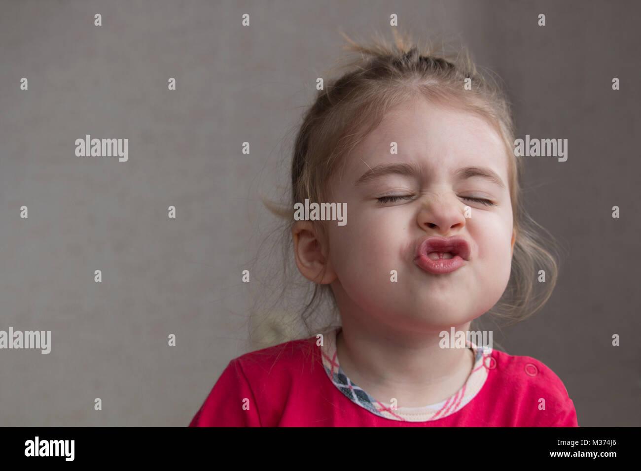 Clouse-up retrato de alegre niña gesticulando y haciendo mueca divertida en la cámara. Has sonrió Imagen De Stock