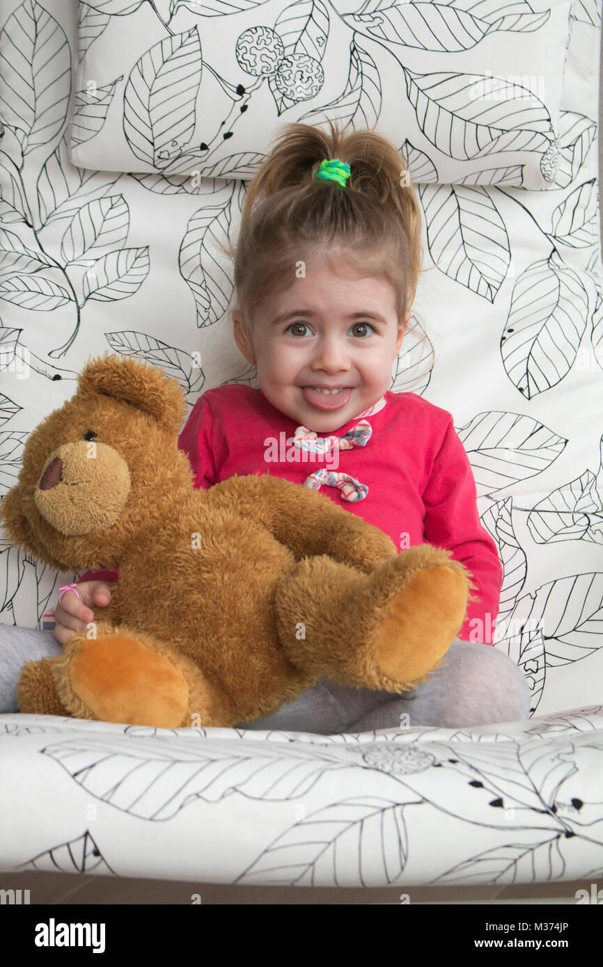 Clouse-up retrato de alegre niña gesticulando y haciendo mueca divertida en la cámara. Imagen De Stock