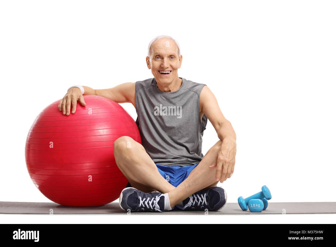 Hombre de edad con una bola de pilates y pesas sentada sobre una colchoneta de  ejercicios 270686029fe3