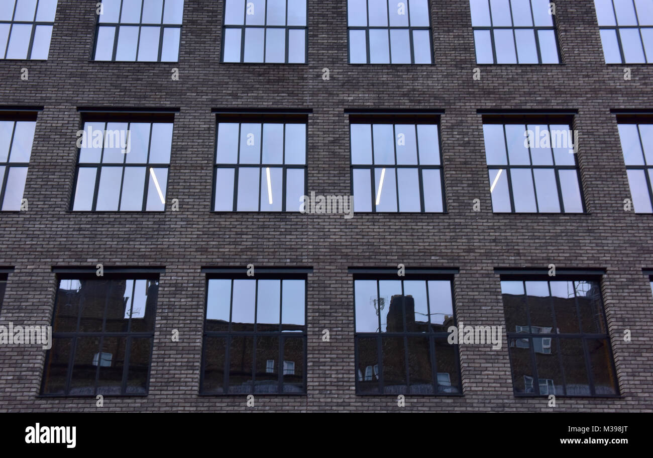 6baf5bc7e3 Un moderno edificio de oficinas incentral Londres con ladrillos de color  oscuro y vidrios polarizados.
