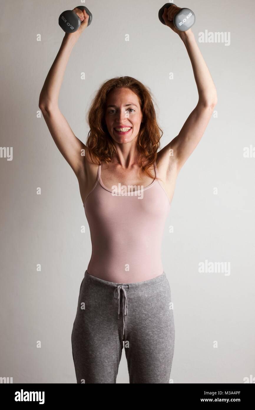 Modelo liberado. Mujer alegre y levantamiento mudos cascabeles sobre su cabeza durante el ejercicio de la fuerza. Imagen De Stock