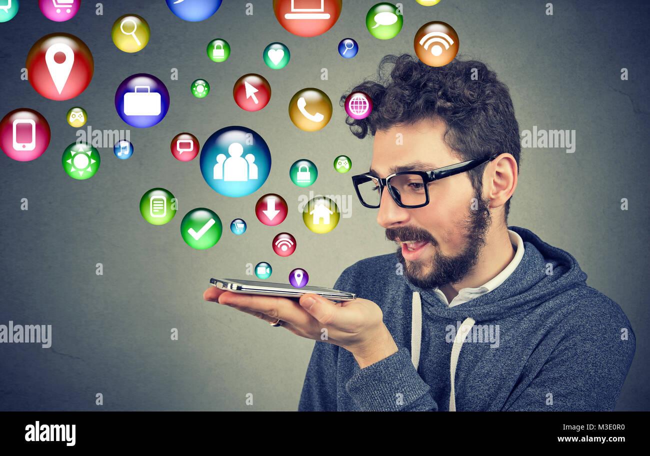 Hombre inteligente hablando por teléfono con un montón de iconos de aplicaciones sobre fondo gris. Imagen De Stock