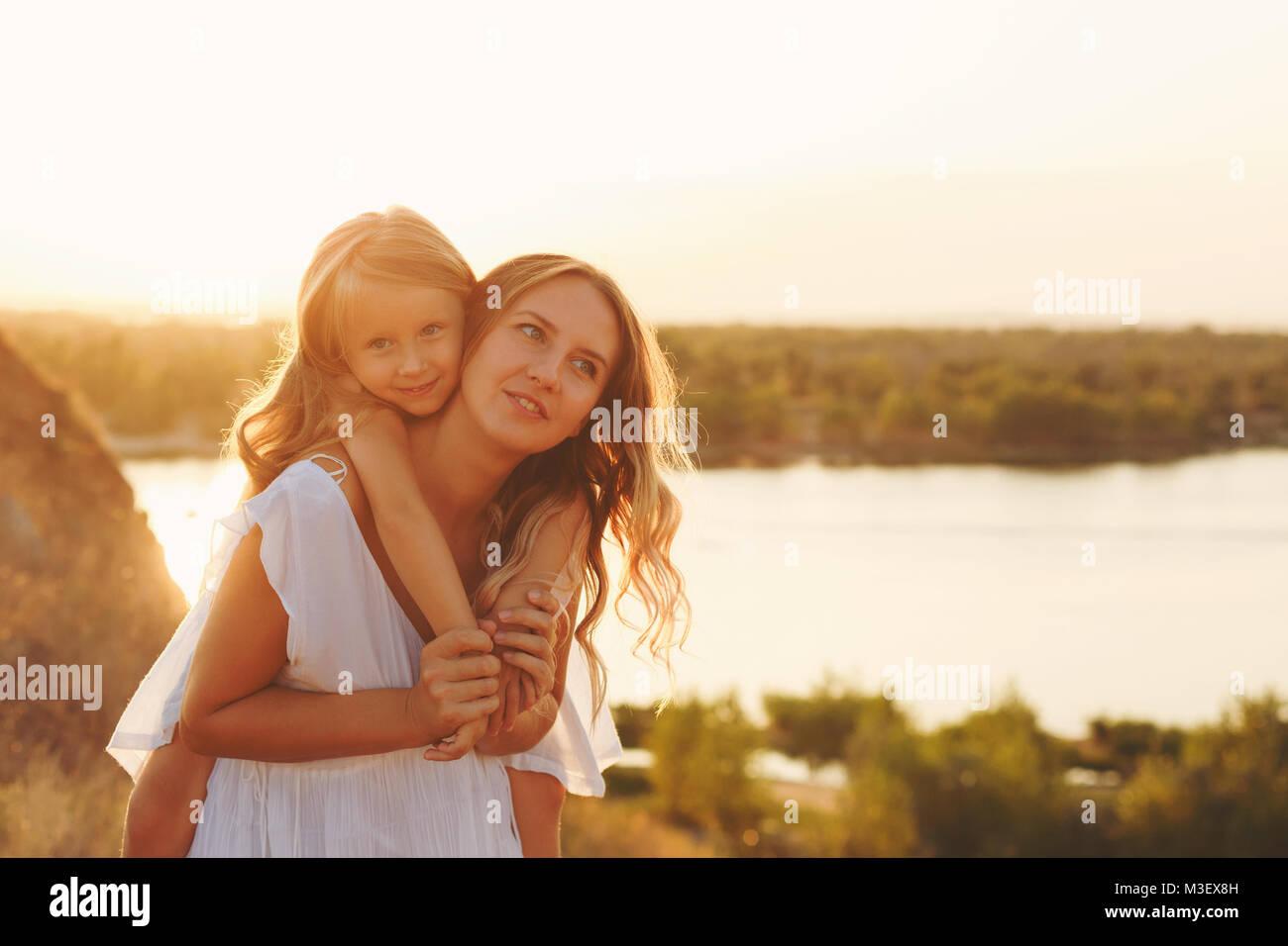 La familia, la madre y la hija en el banco del río. Una niña lleva a su hija sobre los hombros de un piggyback. Imagen De Stock