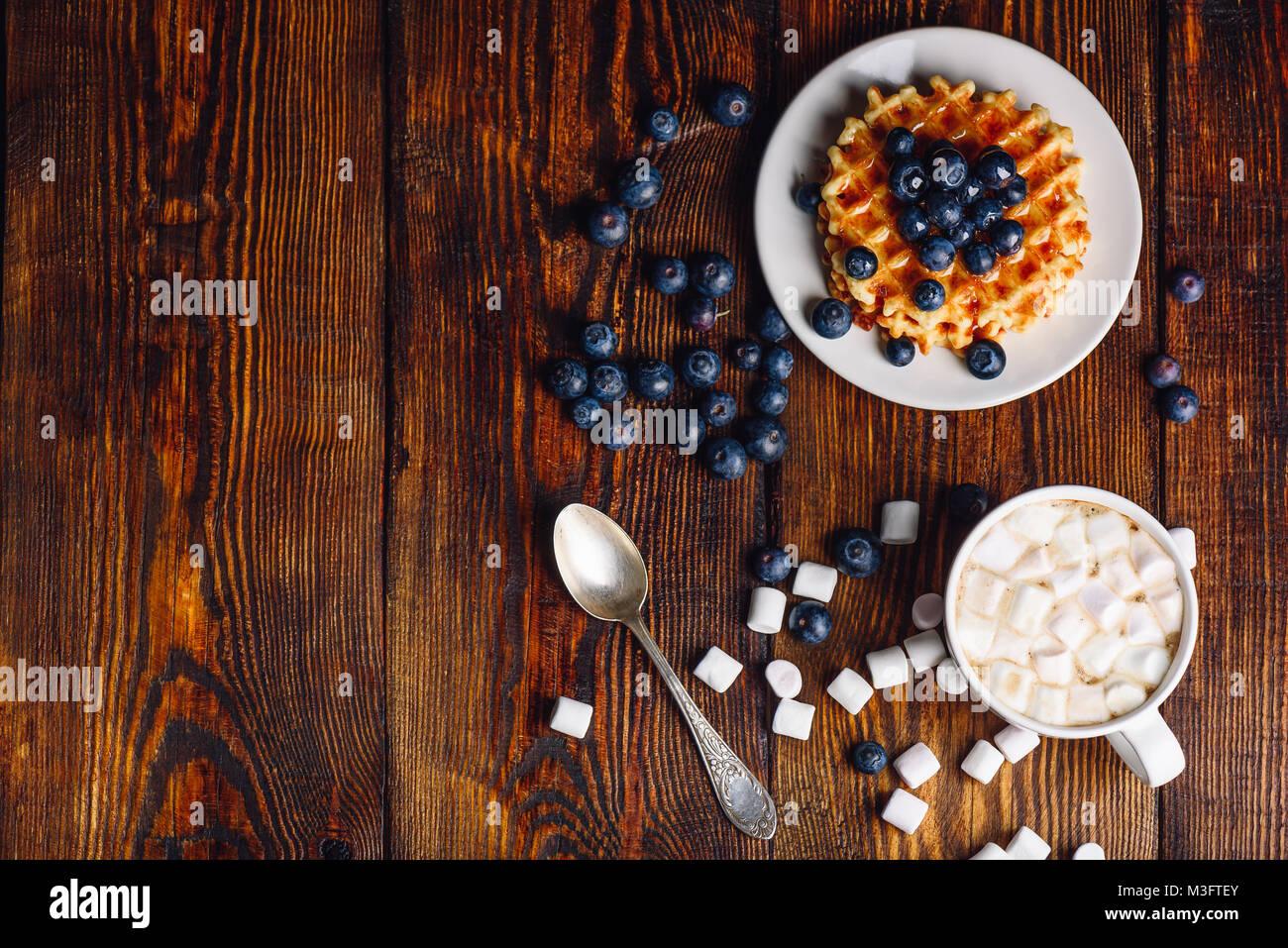 Taza de chocolate caliente con malvavisco y galletas caseras con arándanos frescos y Topping en placa. Copie el espacio a la izquierda. Vistas desde arriba. Foto de stock