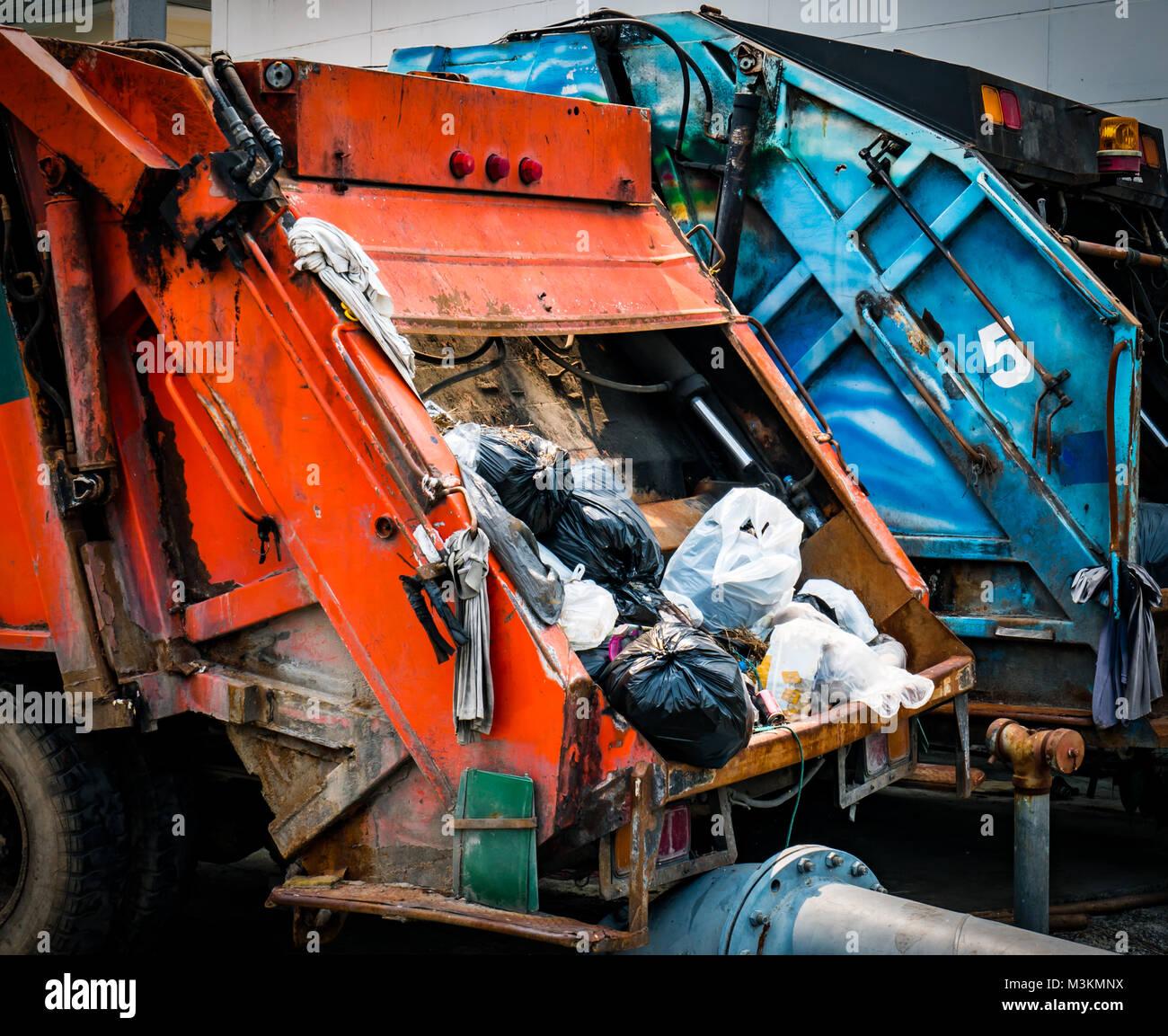 Atrás del viejo camión recolector de basura con residuos. Concepto de gestión de residuos urbanos. Imagen De Stock
