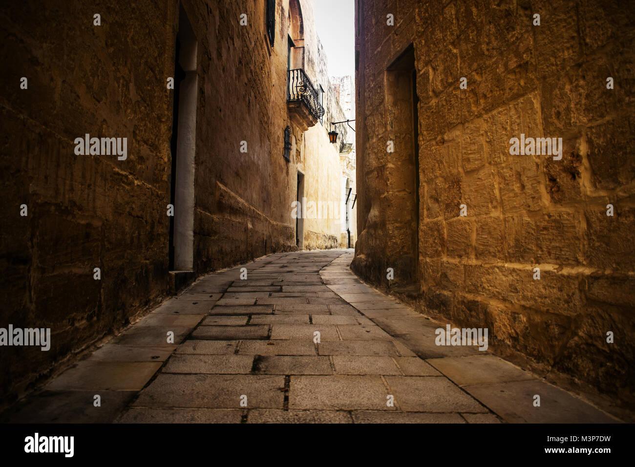 Un típico y angosta carretera históricos incluyendo muros de adoquines en Mdina, Malta. Imagen De Stock