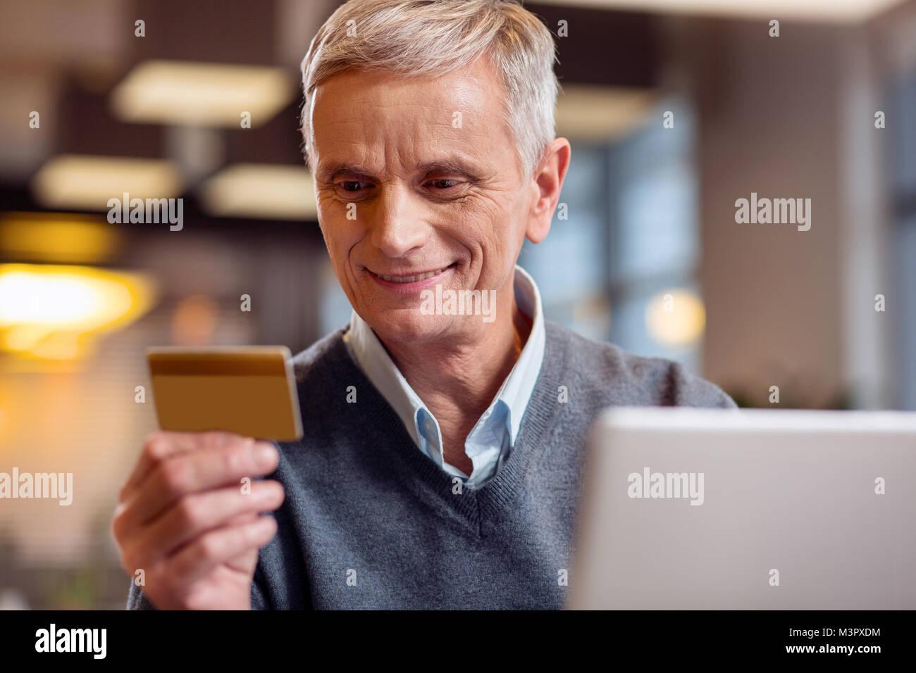 Gay hombre maduro en su número de la tarjeta de lectura Imagen De Stock