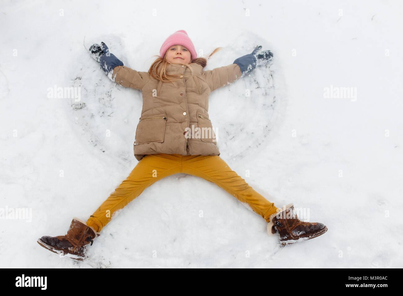 Imagen de chica acostada en la nieve en park Imagen De Stock