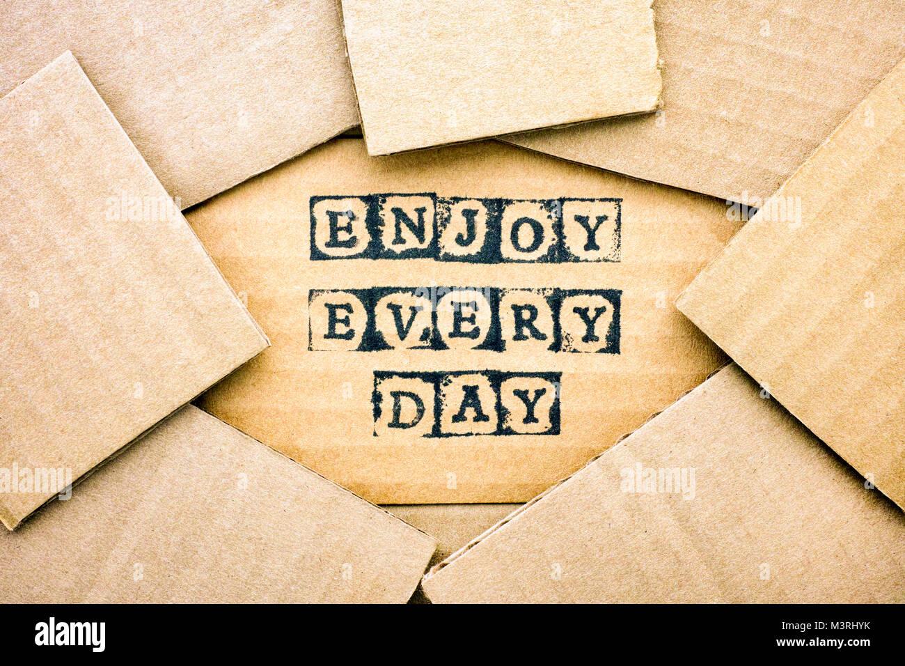 Palabras disfrutar cada día hacen por alfabeto negro sellos sobre cartón con algún trozo de cartón. Imagen De Stock