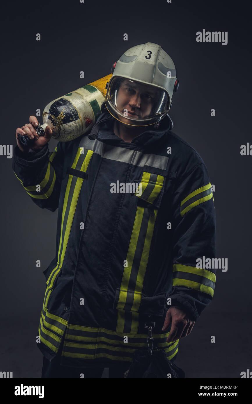 Bombero en casco posee tanque de oxígeno. Foto de stock