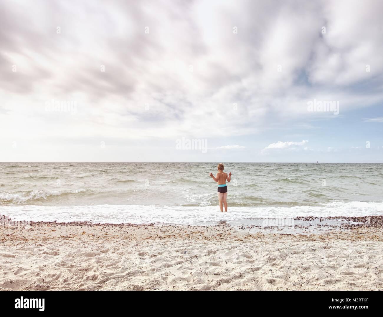 Cabello rubio niño permanecer en frío mar marea. Cabrito en playa de grava de espumosas olas. Día Imagen De Stock