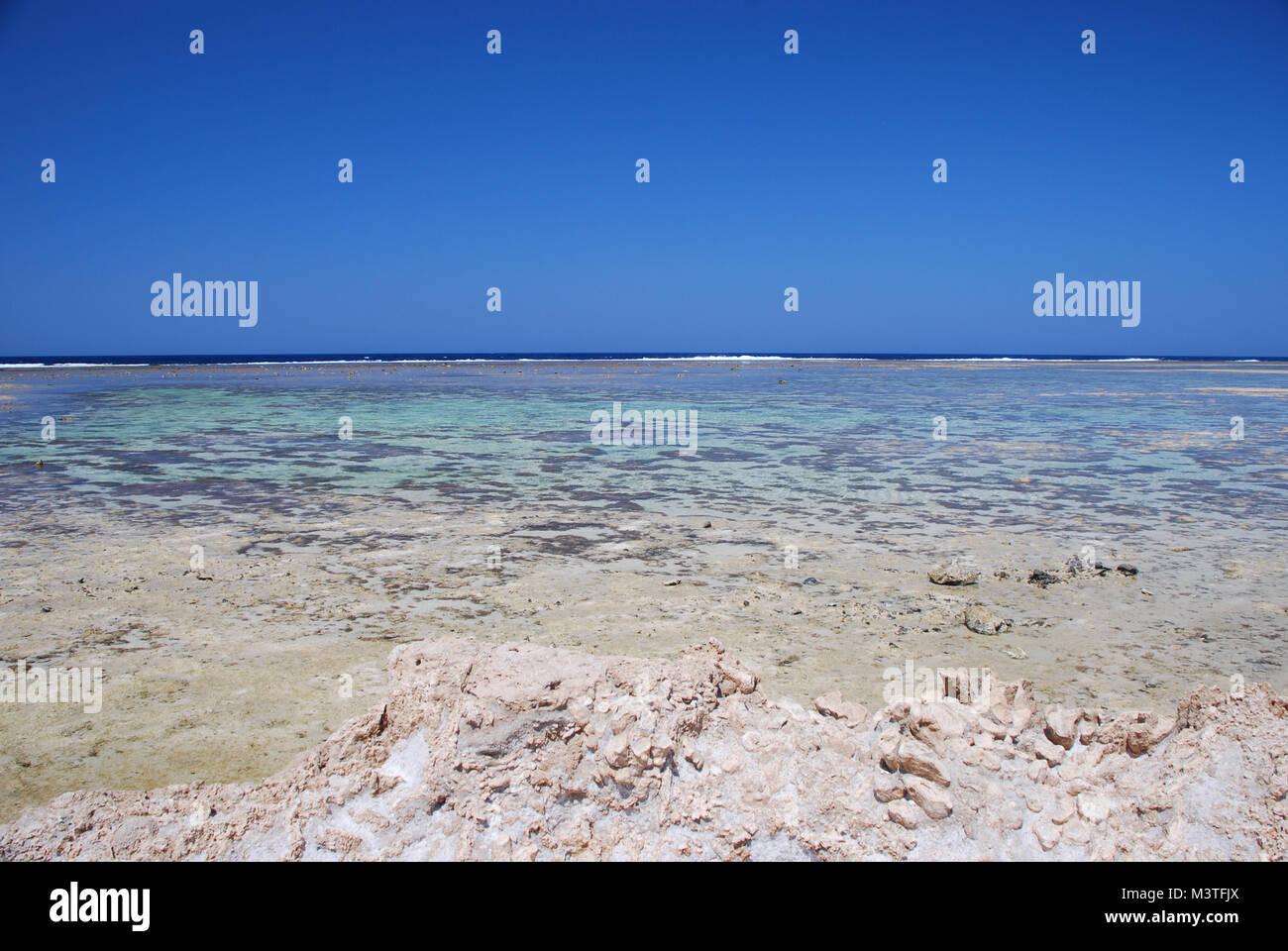 Playa en marea baja sobre el mar rojo, con un cielo azul sin nubes Imagen De Stock