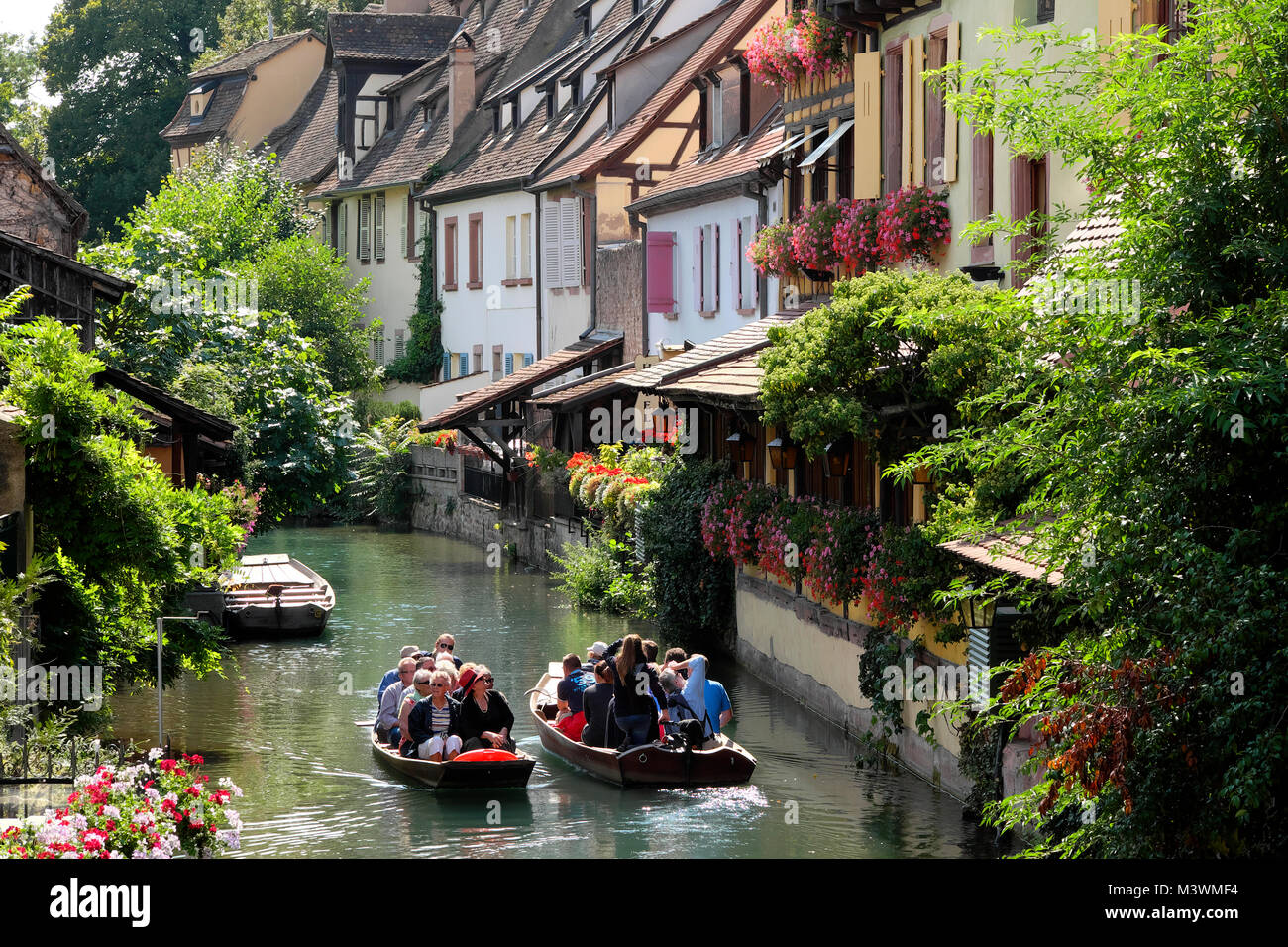 Los turistas en barco por el río en viaje de turismo, Petite Venise / Little Venice, Colmar, Alsacia, Francia Imagen De Stock