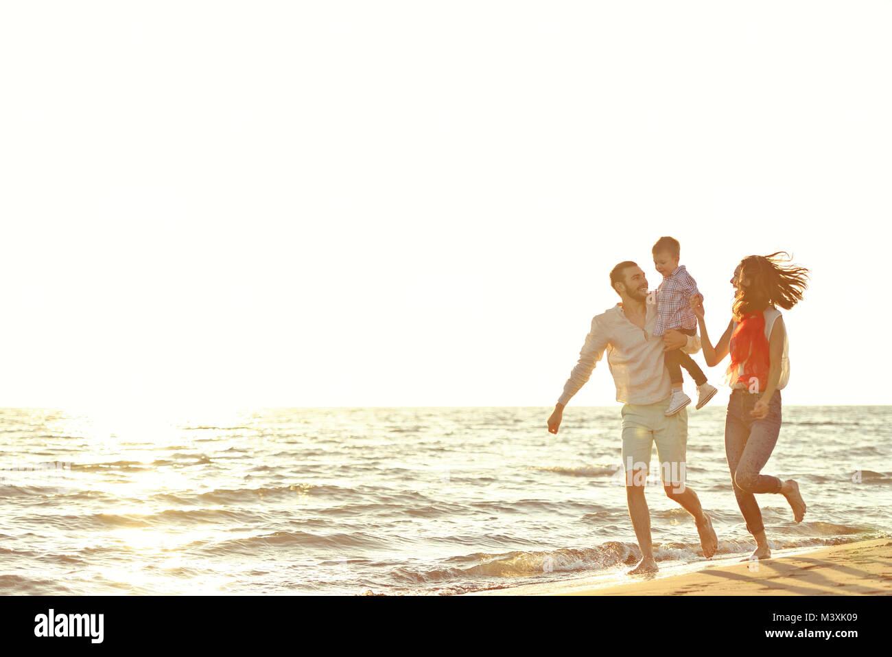 Retrato de familia feliz y el bebé disfrutando del atardecer en el verano ocio Imagen De Stock
