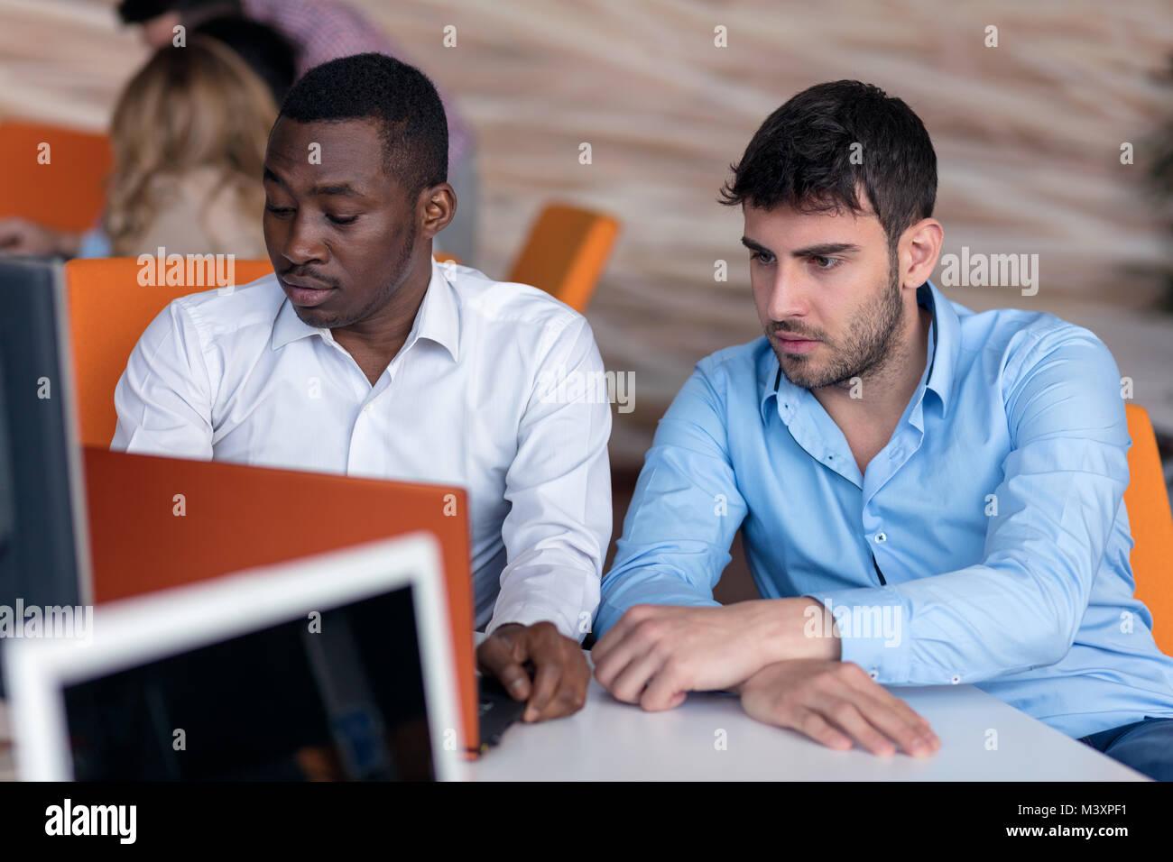 Dos empresario inteligente utilizando workig smartphone y el ordenador portátil en la oficina. Foto de stock