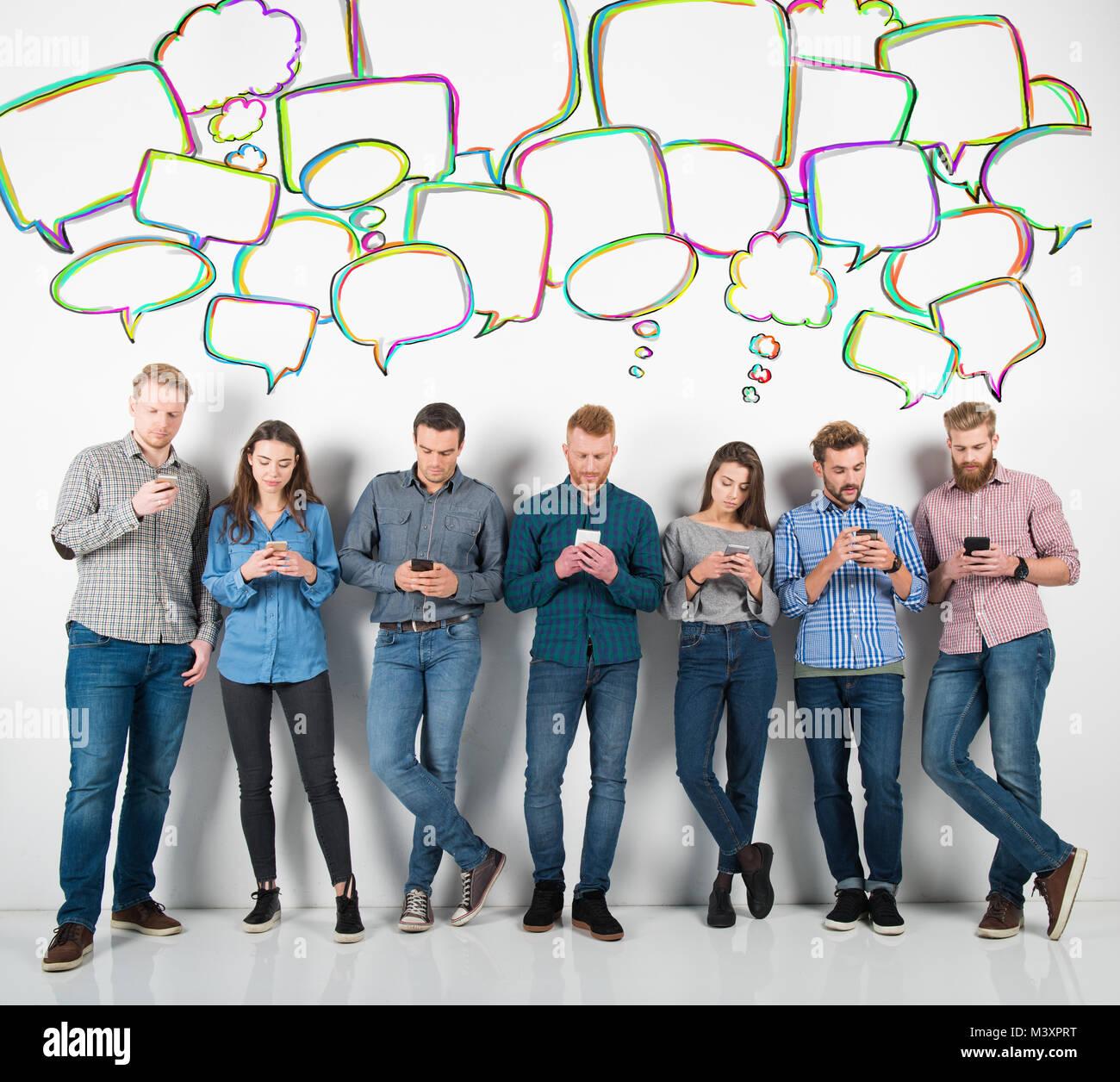 Grupo de niños y niñas vinculadas con sus smartphones. Concepto de internet y de las redes sociales Imagen De Stock