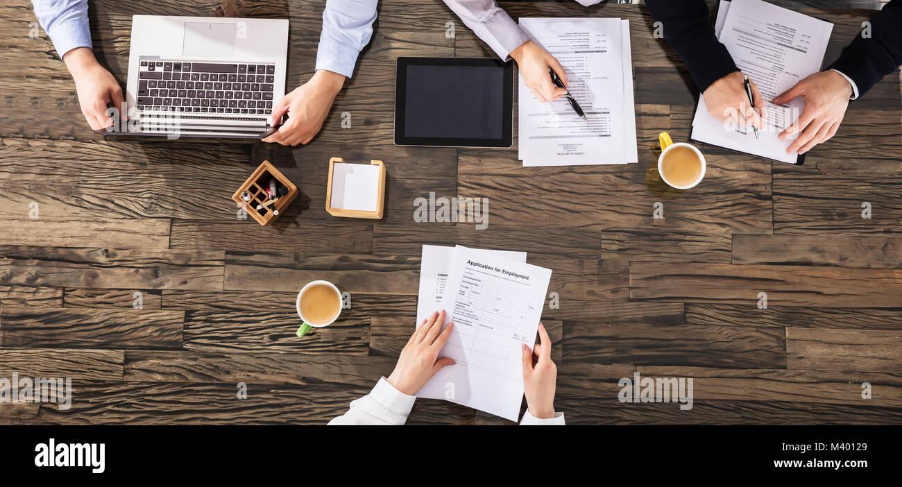 Vista elevada de empresarios teniendo una entrevista sobre el escritorio de madera en la oficina Foto de stock