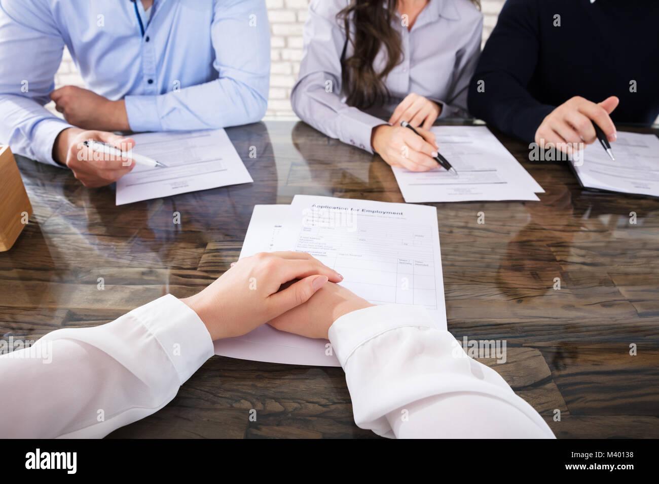 Solicitante delante de los oficiales de reclutamiento corporativo para una entrevista en la oficina Foto de stock