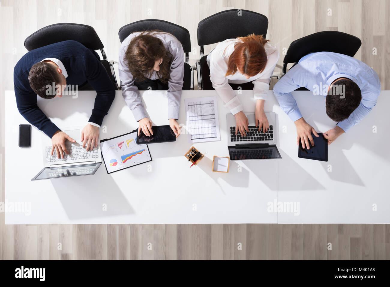 Vista elevada de gente de negocios mediante el uso de dispositivos electrónicos en un escritorio en la oficina Foto de stock