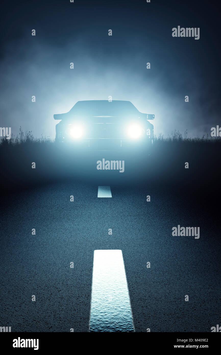 Luces del coche visto desde la parte delantera en una oscura noche brumosa fantasmagóricos y llegando en un camino Foto de stock