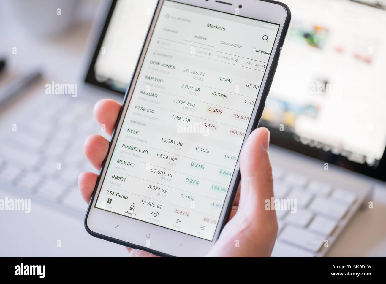 Comprobación de los índices bursátiles en un smartphone Imagen De Stock