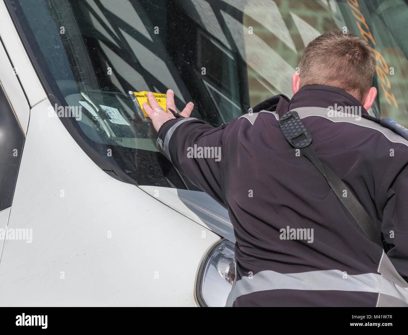Parking warden poniendo un ticket de aparcamiento pena aviso en una ventana de coche en Inglaterra, Reino Unido. Imagen De Stock