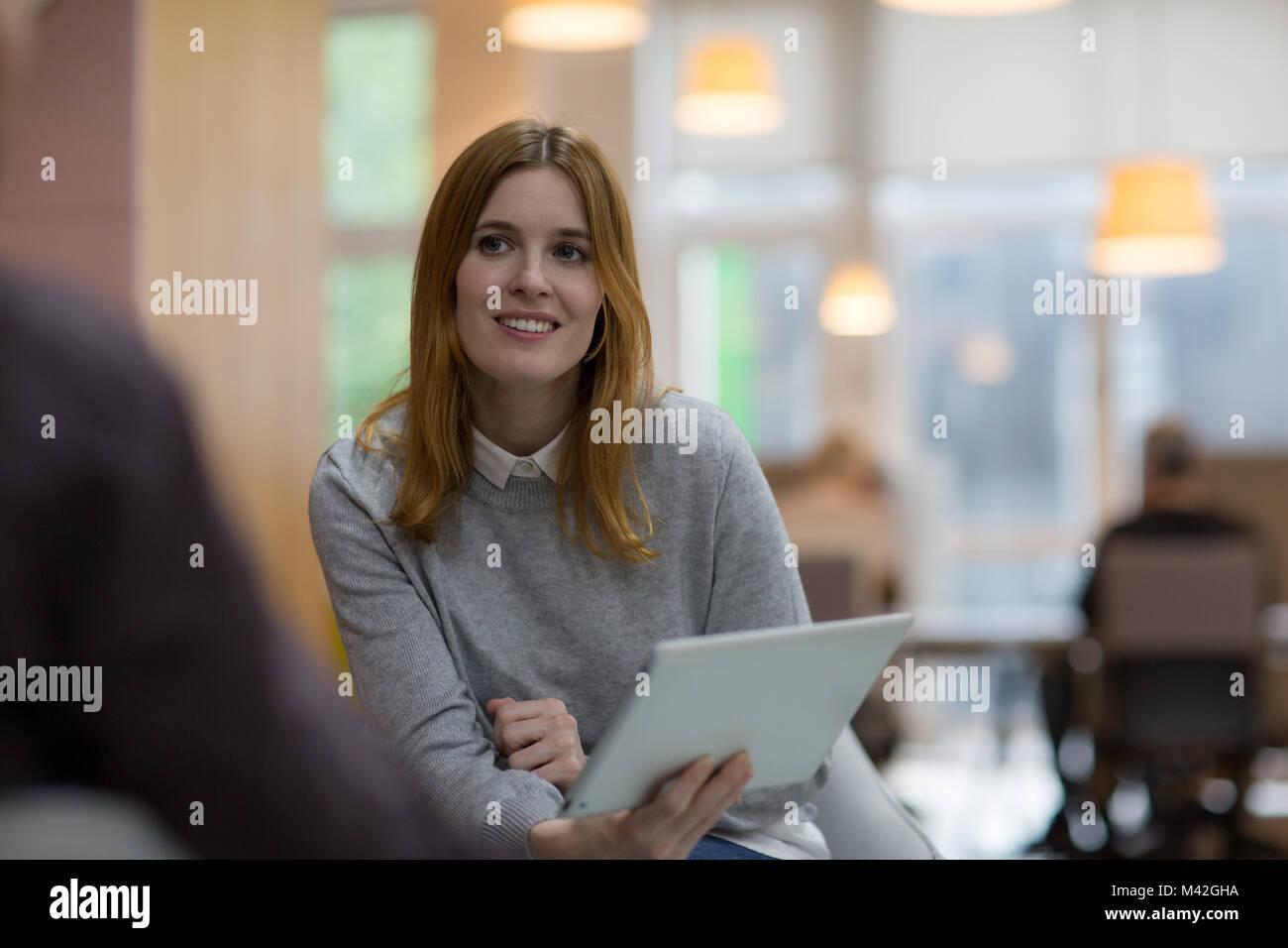 Empresaria en una reunión sosteniendo una tableta digital Foto de stock