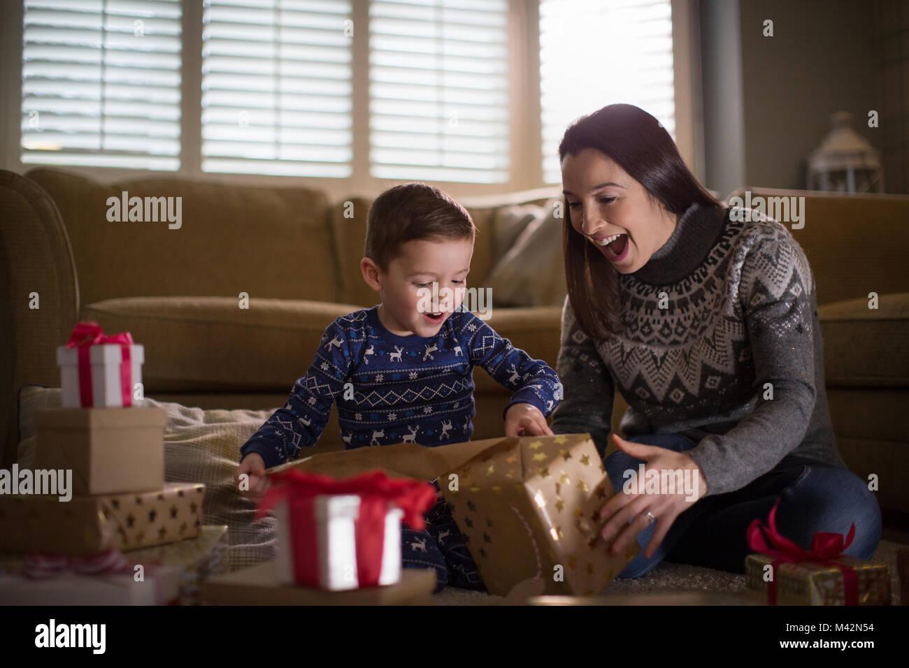 Madre e hijo desenvolviendo regalos de Navidad Imagen De Stock