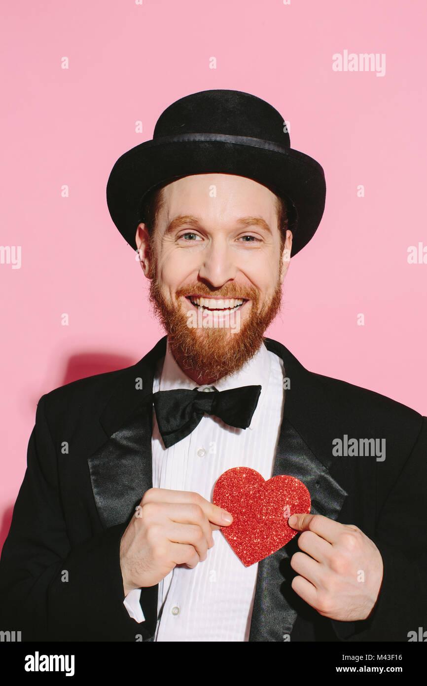 Hombre sonriente en tux y sombrero sosteniendo un corazón rojo sobre su pecho Imagen De Stock