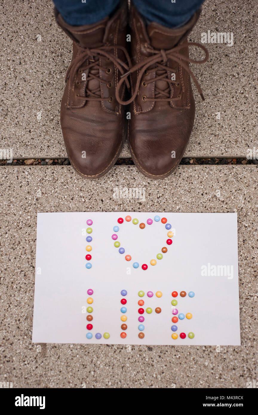 """Papel con las palabras """"Yo amo la vida"""" sobre la tierra y la mujer con zapatos de color marrón cerca Imagen De Stock"""