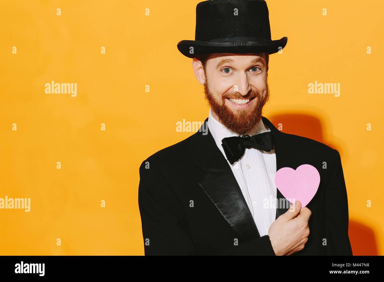 Hombre sonriendo esperanzado con top hat sosteniendo un corazon rosado, mi amor... Imagen De Stock