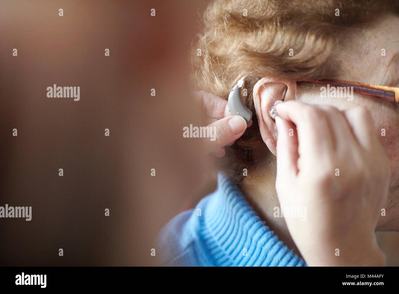 Mujer madura, ayudando a altos mujer insertar audífonos, cerrar, enfoque diferencial Foto de stock