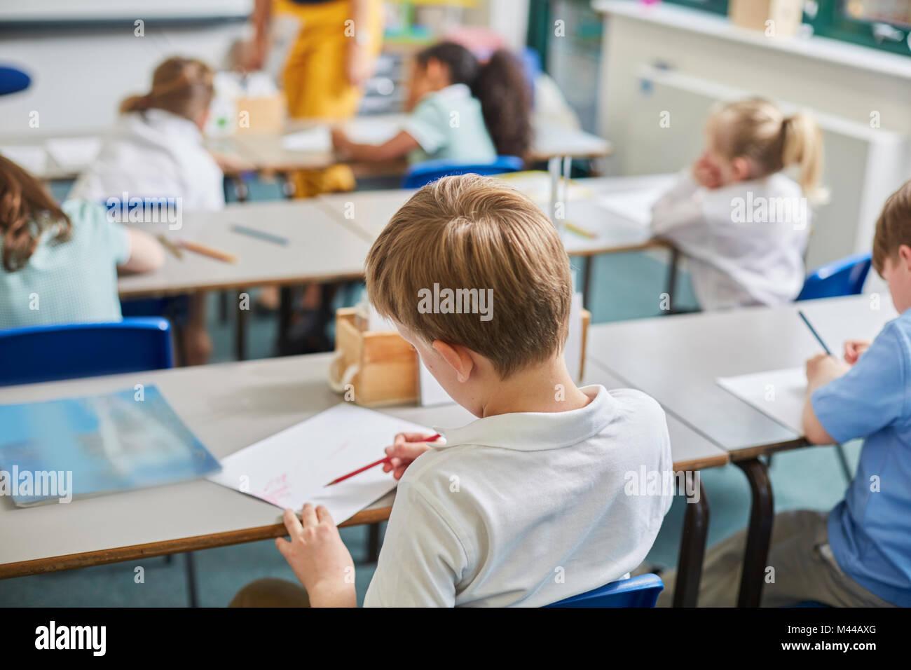 Escolar Primaria y chicas haciendo el trabajo escolar en el aula pupitres, vista trasera Imagen De Stock