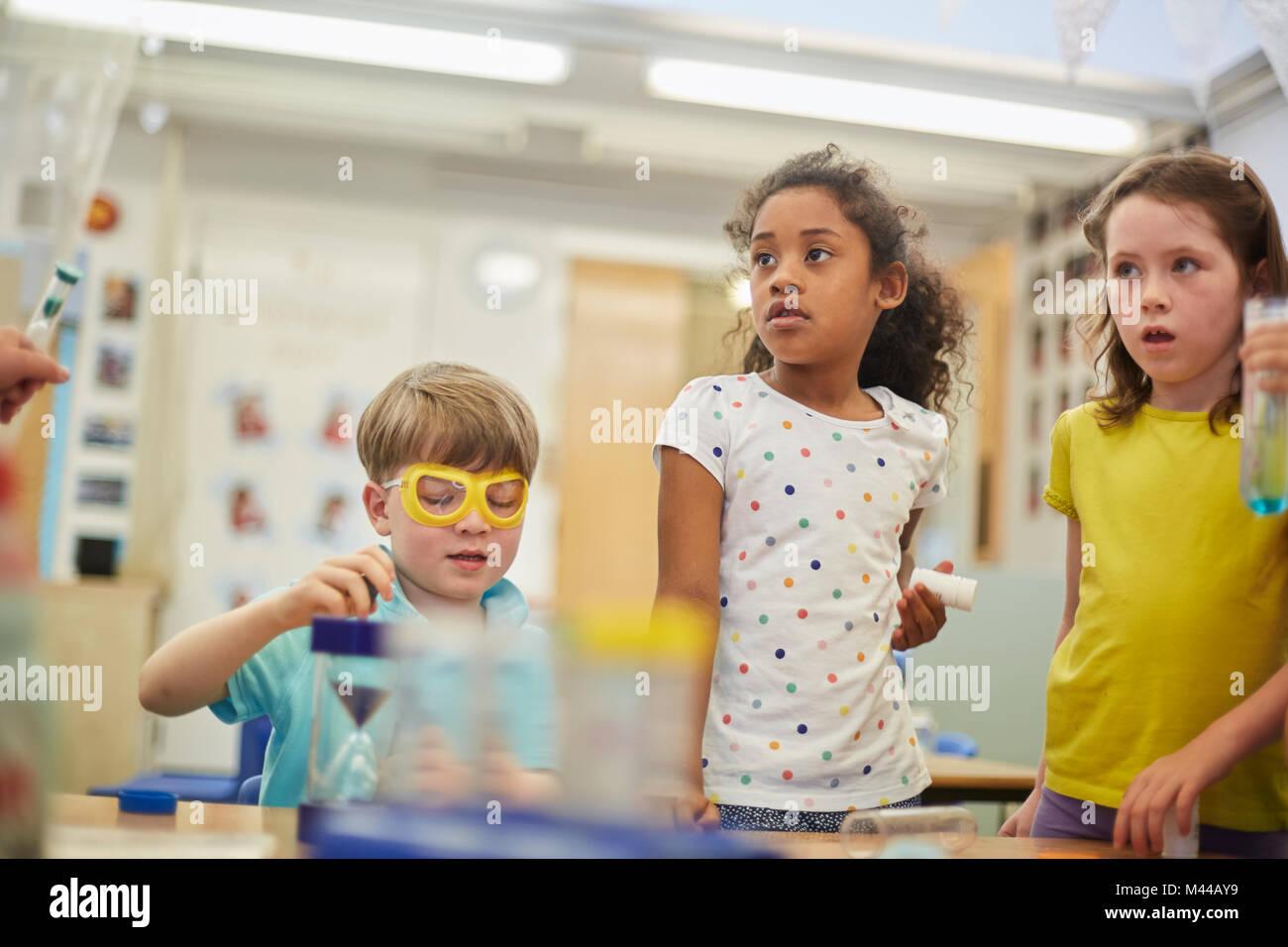 Escolares primarios y muchachos haciendo experimentos en el aula Imagen De Stock
